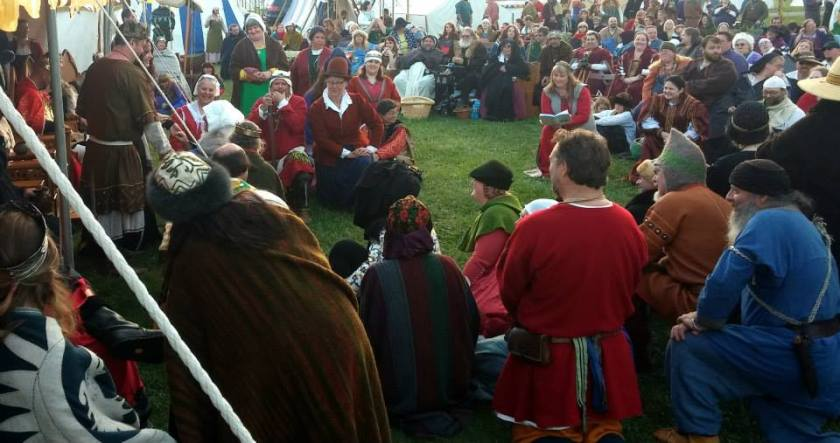 A photo of SCA royal court, many people in historical costumes.