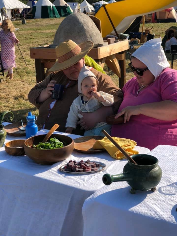 Two women and a baby sitting outdoors at a table for a medieval feast